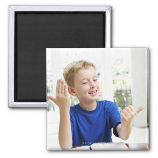 Boy counting on his fingers to complete his magnet