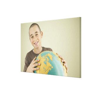 Boy holding globe stretched canvas print