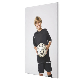 Boy holding soccer ball, smiling, portrait canvas print