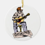 Boy playing acoustic guitar with sheet music christmas tree ornaments