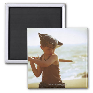 Boy playing pirate, wooden sword magnet
