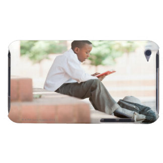 Boy reading on steps outside school, iPod touch cover