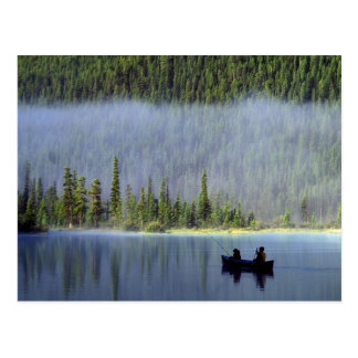 Boys fishing from canoe with mist in postcard