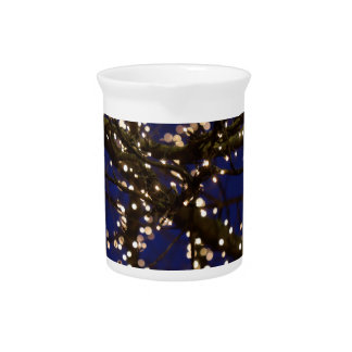 Branches with Christmas lights and a dark blue sky Pitcher