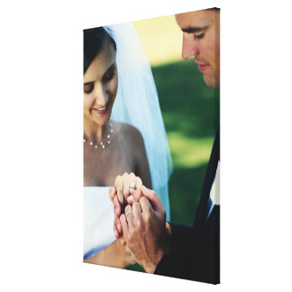 Bride and groom holding hands, close-up canvas print