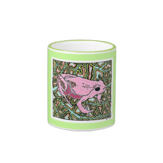 Bright pink tree frog sitting on a blue and gold l coffee mugs