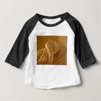 Brioche on a wooden table with granulated sugar baby T-Shirt