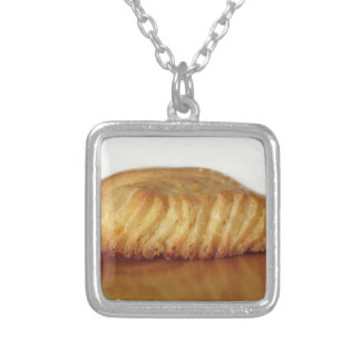 Brioche on a wooden table with granulated sugar silver plated necklace