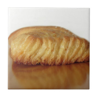 Brioche on a wooden table with granulated sugar tile