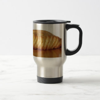 Brioche on a wooden table with granulated sugar travel mug