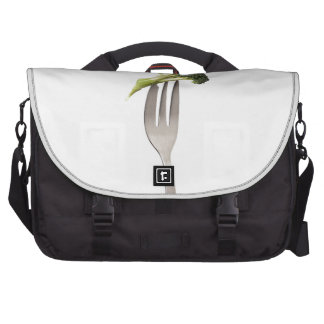 Broccoli held by a fork laptop commuter bag