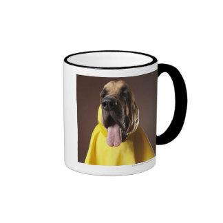 Brown bloodhound dog wearing yellow raincoat ringer mug