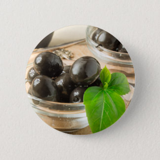 Brown pickled olives on the old wooden background 6 cm round badge