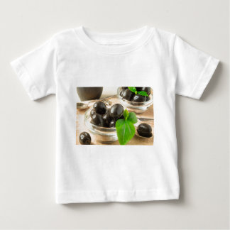 Brown pickled olives on the old wooden background baby T-Shirt