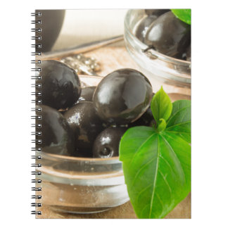 Brown pickled olives on the old wooden background notebooks