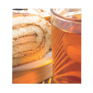 Brown sponge cake and cup of hot tea notepad