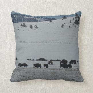 Buffalo grazing on snow covered mountain throw pillow