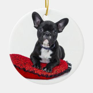 Bulldog puppy sitting on red heart shaped cushion round ceramic decoration