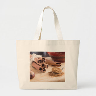 Bunch of cinnamon sticks and vintage silver spoon large tote bag
