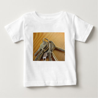 Bunch of worn house keys on wooden table baby T-Shirt