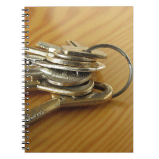 Bunch of worn house keys on wooden table notebooks