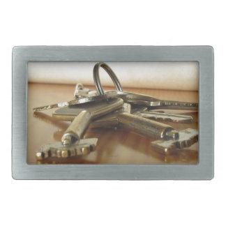 Bunch of worn house keys on wooden table rectangular belt buckle