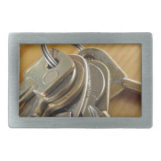 Bunch of worn house keys on wooden table rectangular belt buckles