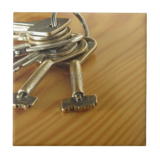 Bunch of worn house keys on wooden table small square tile