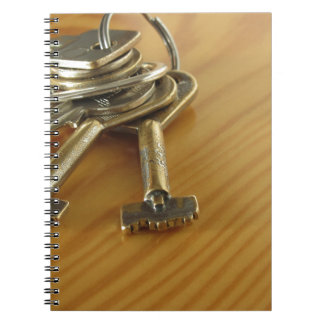 Bunch of worn house keys on wooden table spiral notebook