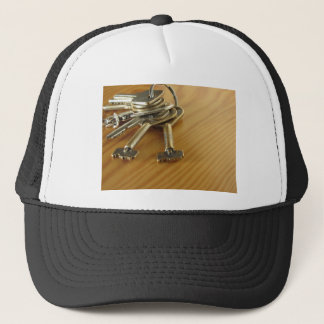 Bunch of worn house keys on wooden table trucker hat