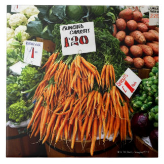 Bunches of carrots and vegetables on market large square tile