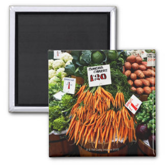 Bunches of carrots and vegetables on market square magnet