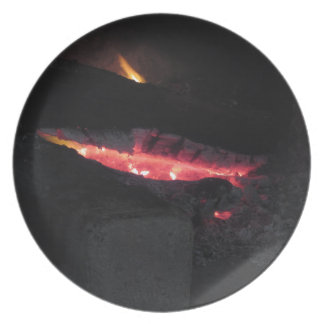 Burning fireplace with fire flames on black plate