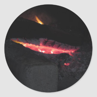 Burning fireplace with fire flames on black round sticker