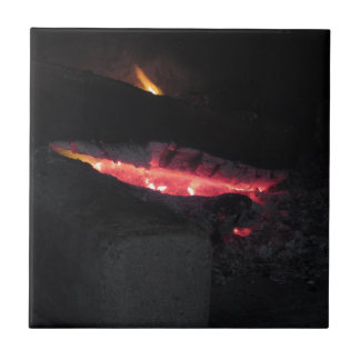 Burning fireplace with fire flames on black small square tile