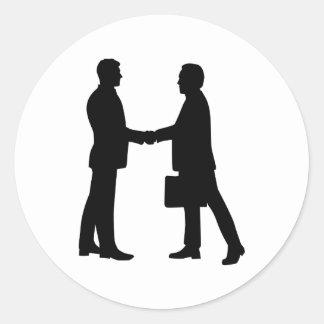 Business men shake hands round sticker