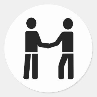 Business men shaking hands round sticker