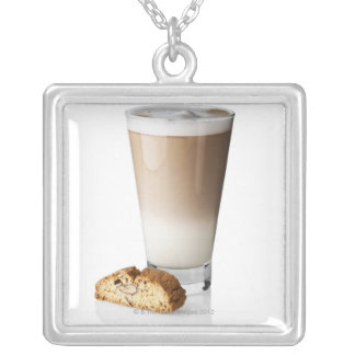 Caffe latte with biscotti, on white background, silver plated necklace