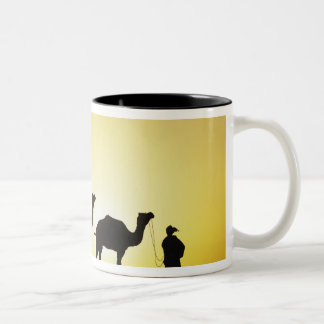 Camels and camel driver silhouetted at sunset, 2 Two-Tone mug
