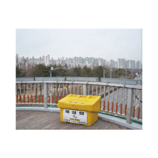 Canvas print of yellow bin against tower block sky