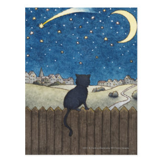 Cat on a fence looking at night sky above city postcard