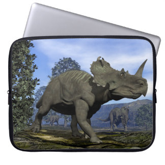 Centrosaurus dinosaurs walking among magnolia tree laptop sleeve