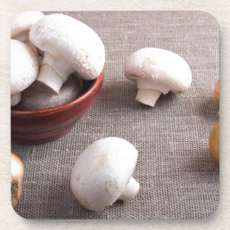 Champignon mushrooms and onions on the table coaster