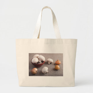 Champignon mushrooms and onions on the table large tote bag
