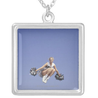 Cheerleader jumping, low angle view, portrait silver plated necklace