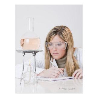 Chemist looking at Bunsen burner Postcard