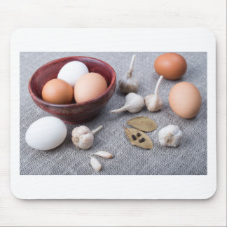 Chicken eggs and garlic and spices on the kitchen mouse pad