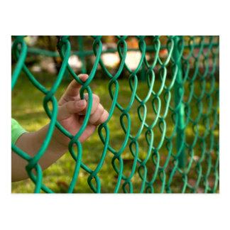 Child finger on fence postcard
