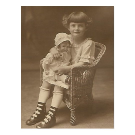 child sitting in chair holding doll post card