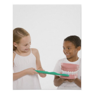 Children with a model set of teeth and oversized poster